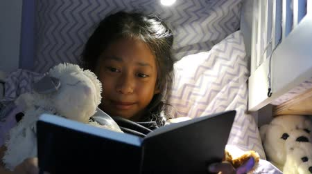 czytanie : A cute little Asian girl enjoys spending time in her home made fort in her bedroom reading and using her device and hanging out with her puppy.