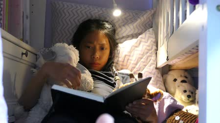 köpek yavrusu : A cute little Asian girl enjoys spending time in her home made fort in her bedroom reading and using her device and hanging out with her puppy.