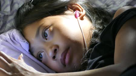 věrný : A very sleepy little Asian girl enjoys spending time in her home made fort in her bedroom listening to music and watching videos on her device while trying hard to not fall asleep.