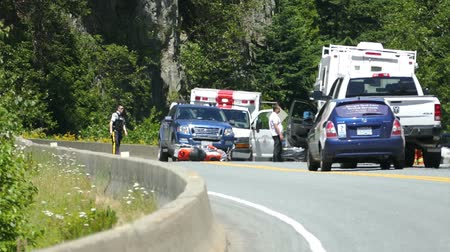 A serious motorcycle accident occurs on the Sea to Sky Highway on the way to Whistler and police and paramedics fight to save the bikers life while pedestrians patiently wait.