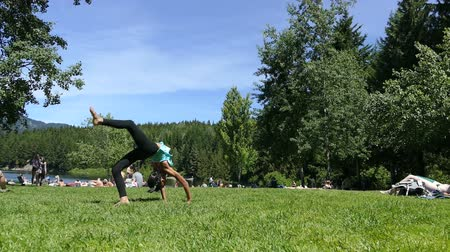 A cute little 10 year old Asian girl practices doing back flips at the lake on a beautiful summer's day! Stock mozgókép