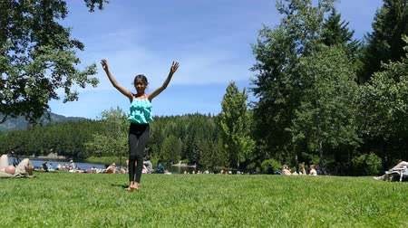 A cute little 10 year old Asian girl practices doing back flips at the lake on a beautiful summers day! Stock mozgókép