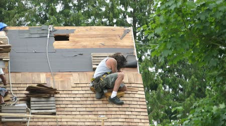 A scruffy roofer hammers down a cedar shake shingle on an old home that is being restored. Wideo