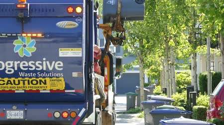 A new modern garbage truck comes to collect the trash in a suburban townhouse community. Wideo