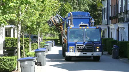A new modern garbage truck comes to collect the trash in a suburban townhouse community. Stock mozgókép