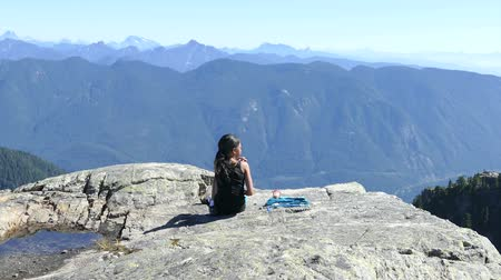 A cute little 11 year old Asian girl successfully climbs Mount Seymour with stunning views looking east from the city of Vancouver on a gorgeous summer day.