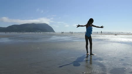A cute little 11 year old Asian girl practices doing back hand springs at the beach on a beautiful summer's day!