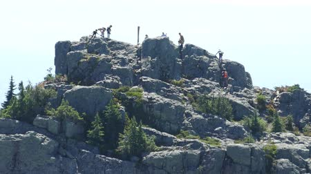 wspinaczka górska : A shot of a bunch of hikers and mountain climbers arriving at the top of a mountain peak on a beautiful summer day. Wideo