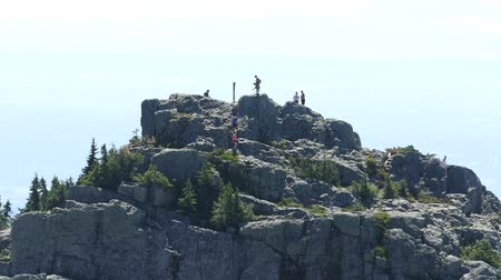 A shot of a bunch of hikers and mountain climbers arriving at the top of a mountain peak on a beautiful summer day. Wideo