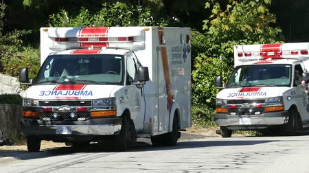 Two ambulances and paramedics respond at the scene of an accident in the city.