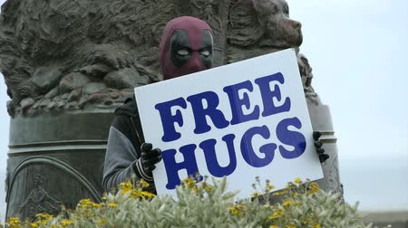 A man wearing a Deadpool mask holds a sign offering free hugs to the public. Wideo