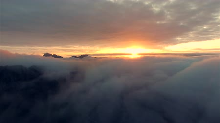 над : Scenic flight on late evening above clouds viewing midnight sun on Lofoten islands in Norway. Aerial 4k Ultra HD.