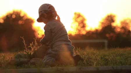 сумерки : Mother and baby playing in the setting sun. Hands close-ups of the child.