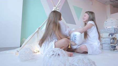 almofada : Little girls dressed in white pillow fight