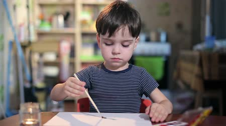 kitchen paper : boy at the table draws with a brush Stock Footage