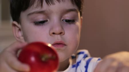 feed on : Cheerful boy playing with  red apples.