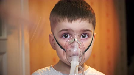 ar : Boy makes inhalation, using a mask.