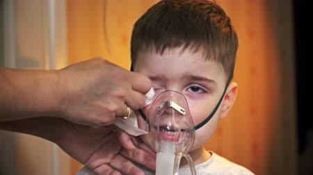 грипп : Boy makes inhalation, using a mask.