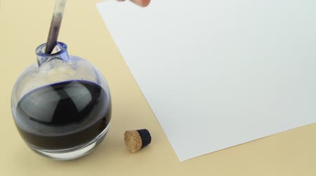 kartka papieru : Hand writing on parchment with quill pen and glass ink bottle.
