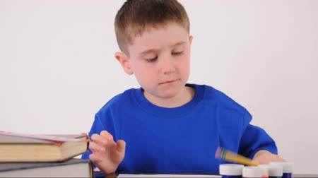 сердитый : A young school boy is tired from homework and then starts writing at his desk with a pencil on a white background for an education or academic concept.