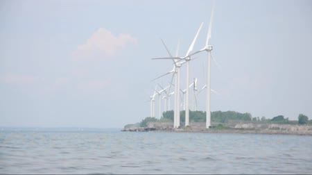 utilidade : Wind Turbines are creating alternative energy on a water shore for a clean environment concept.