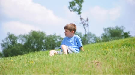 avançar : A young boy is sitting on a green grass hill and thinking on a hot summer day for a childhood or relaxation concept.