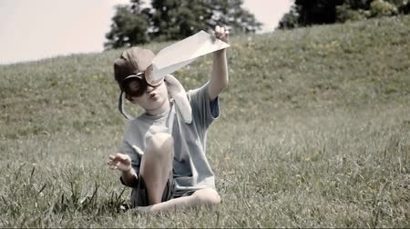 paper airplane : A boy is flying a paper airplane in a field with an antique feel for a time or memory concept. Stock Footage