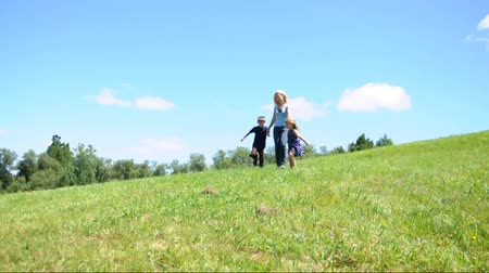 gün : A family is running down a green grass nature hill. The mother is holding the daughter and sons hands for a happiness or freedom concept. Stok Video