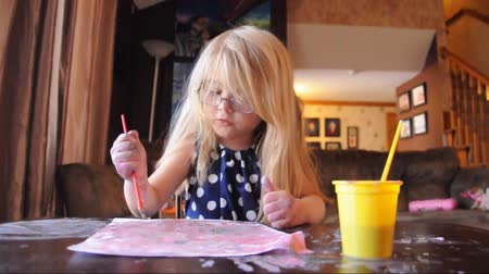 nepořádek : A preschool girl is painting on messy white paper at desk in her house for an artistic or creative concept.