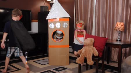 rakieta : A mother and her children are playing with a cardboard box of a rocket ship in their home and pretending they are in space for an activity or entertainment concept.