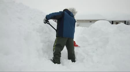 deep snow : A man is shoveling a lot of snow from a winter blizzard storm. There is a huge pile of white snow on the sidewalk.