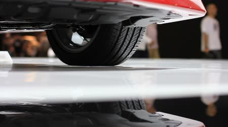 auto show : This is a dynamic rotating shot of the undercarriage of a sports car at a car show.