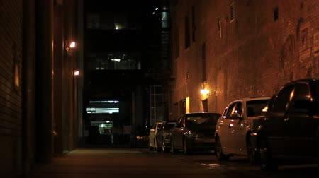 mroczne : A typical alley in downtown Calgary.  Lighting makes it look very sinister.  Perhaps the site of a crime scene.  Great for establishing a dark mood in the city.