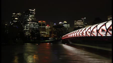 в центре города : This is a night time lapse scenic featuring downtown Calgary, Peace Bridge, and the Bow River