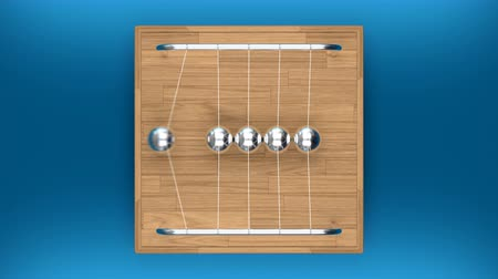 Looped animation of Newtons cradle on a table, top view