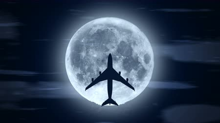 Silhouette of passenger airplane flying over moon in cloudy night