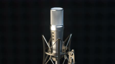 Camera approaching close to professional microphone in a dark sound recording studio. Close up.
