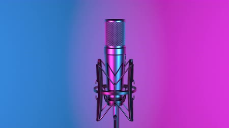 Professional microphone lit by cyan and magenta spot lights against changing colorful background
