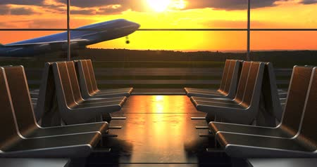 Passenger airplane departure as seen from airport through departure hall windows with scenic sunset on background.