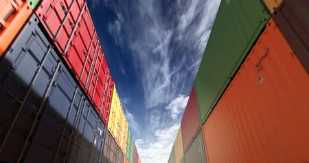 Cargo shipping container stacks under cloudscape. Industrial containers are excellent for cargo import export shipment. Camera seamlessly moves thru cargo boxes of different transportation companies Stock Footage