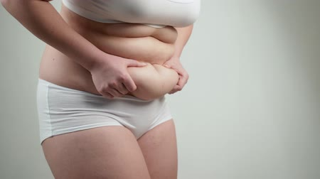 squeeze : Woman in white underwear holds her belly fat.