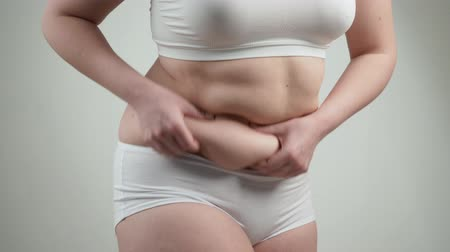 Woman in white underwear holds her belly fat.