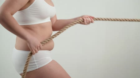 corda : Fat woman pulling a rope. Fighting excess weight concept.