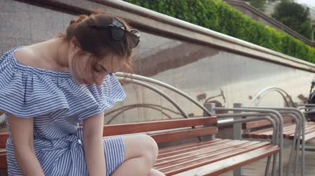 fasteners : Young woman fastens sandals sitting on the bench.