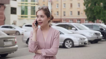 сплетни : Young woman talking on her cell phone on the street.