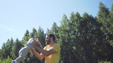 kabarık : Young father spin his little daughter outdoors.