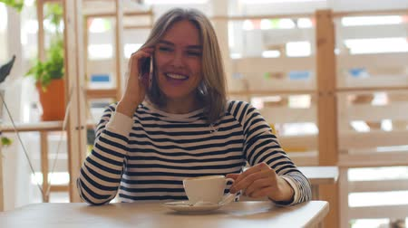 сплетни : Beautiful young woman speaks on the phone and smiling. Стоковые видеозаписи