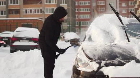 Man clearing his car with brush from snow in the yard.