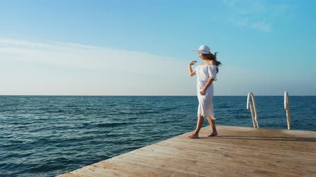 Young woman walking on a wooden pier, looking at the sea.