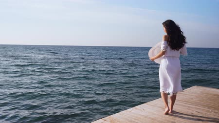 Young woman stands on wooden pier, looking at the sea. Wideo